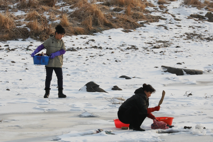 North Korean women as they wash clothes in the frozen Yalu River