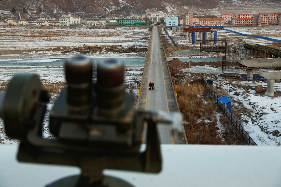 Women, photographed from the Chinese side of border, are seen from a viewing point used by tourists to look into North Korea,