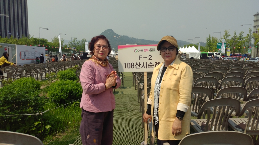 Ha Sa-jin, 70 (left), and Jang Hye-song, 71 (right), stand in Gwanghwamun Square in front of a Buddhist festival on the day of the Inter-Korean Summit on April 27, 2018. Jang fled from North Korea with her family when she was 2 years old.