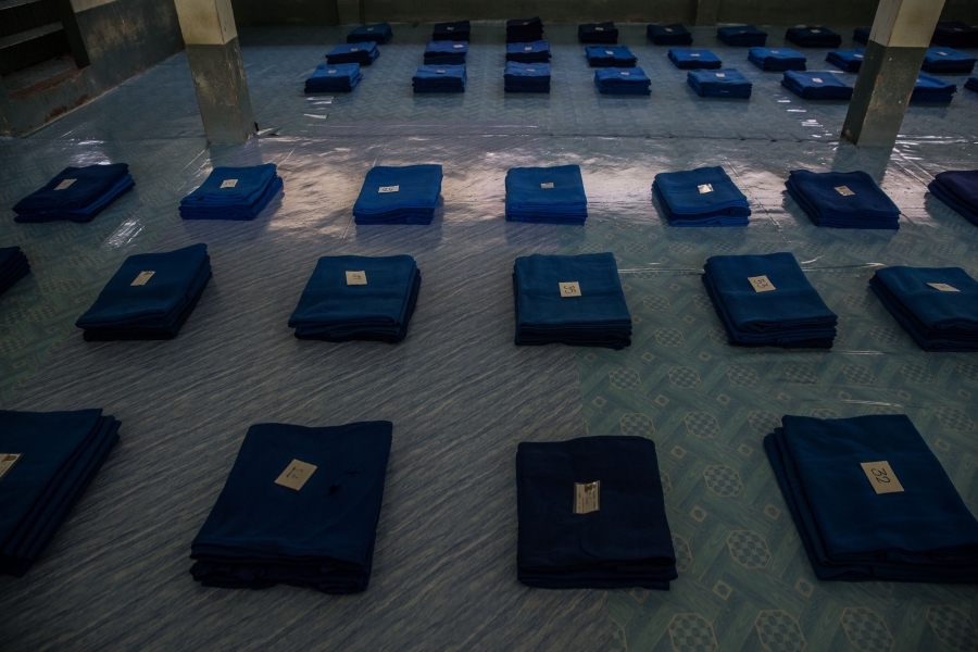 Blue blankets are folded in tidy rows across a carpet, with a number placed atop each one.