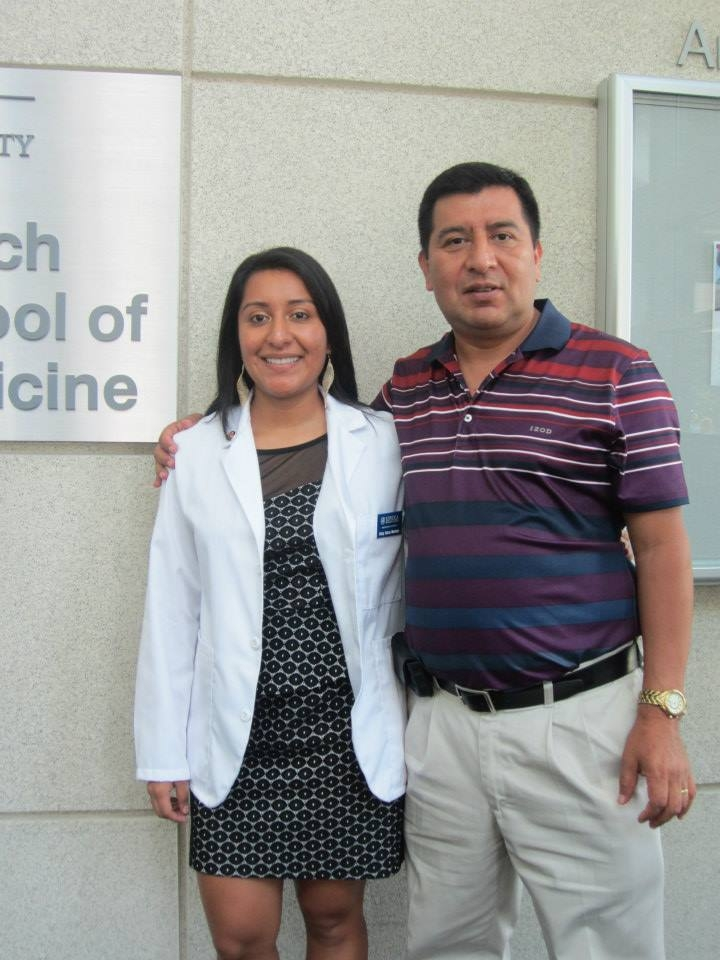 Woman in white coat smiling, posing with older man
