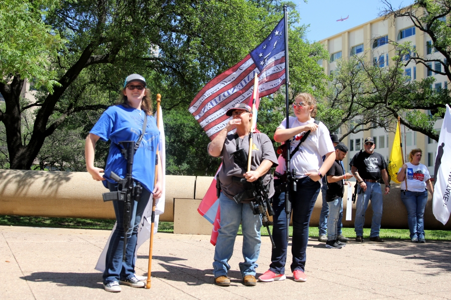 "Emily (far left) and Nicole Defosse (far right, holding the ""2nd Amendment American Flag"") held unloaded AR 15s as they stood in counter-protest roughly 50 yards away from a rally held in support of stricter gun control legislation outside of city hall on"