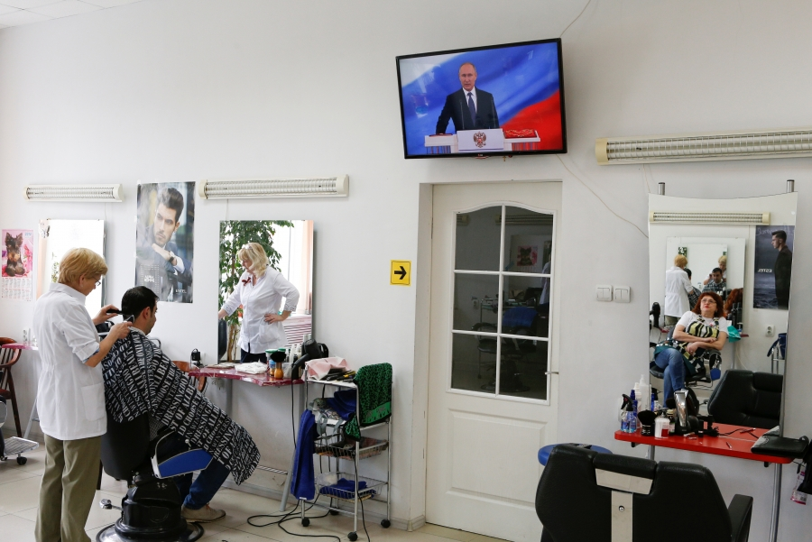 A hairdresser watches Vladimir Putin's inauguration ceremony at a salon in Stavropol, Russia, May 7, 2018.