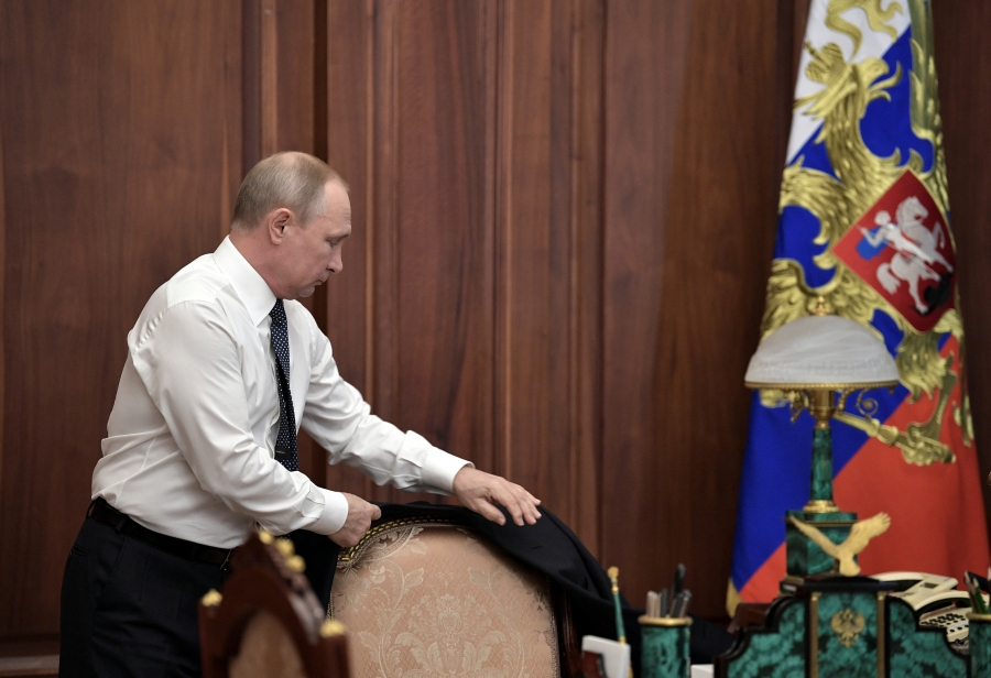 Russian President Vladimir Putin stands up from his desk and prepares to put on his suit jacket before his inauguration ceremony at the Kremlin in Moscow, Russia, May 7, 2018.