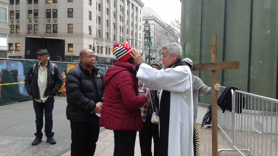 Man giving blessing in front of wooden cross on sidewalk