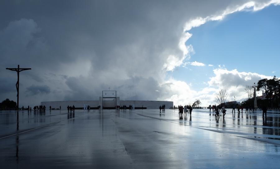 Visitors dot the massive plaza outside the Shrine of Fatima megachurch, under stormy skies