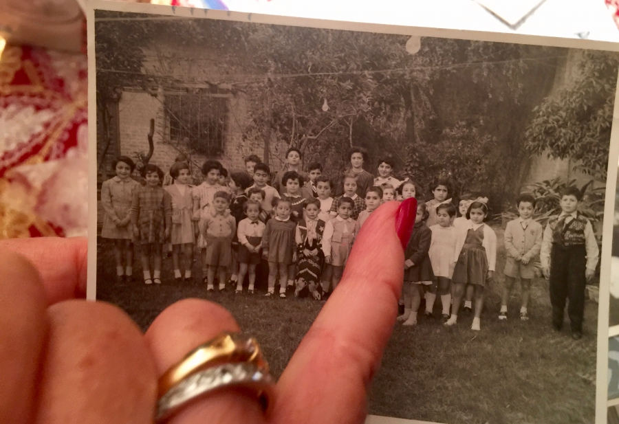 Lisette Shashoua points out classmates in a school photo from her childhood in Baghdad. She and her friends consider the photo album a treasure. When they fled Iraq, most Jewish families were forced to leave everything behind.