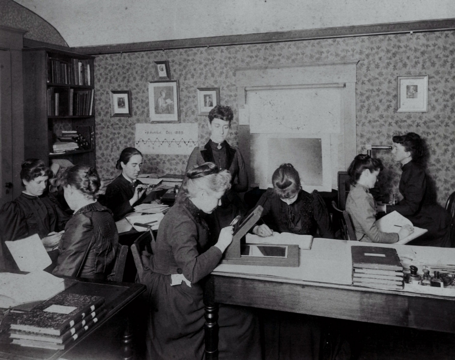 A group of women are sitting in a tiny room, some holding magnifying glasses, bent over boxes studying the glass plates. One stands in the center of the room, overseeing them. This is Henrietta Fleming.