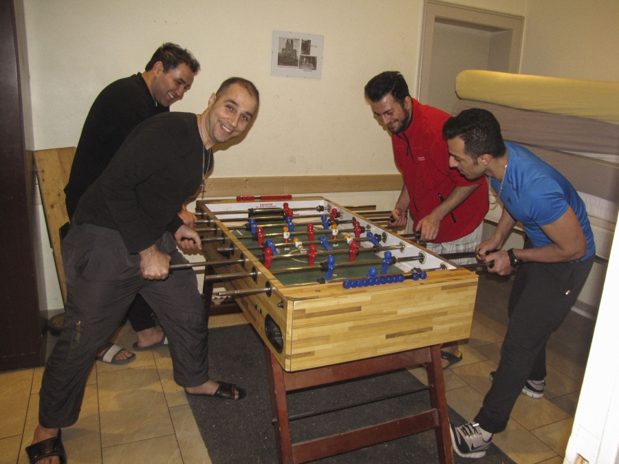 Foosball is one diversion for the residents of the Evangelical Lutheran Church in Berlin. Left to right: Ali, Amir, Saeed and Ali.
