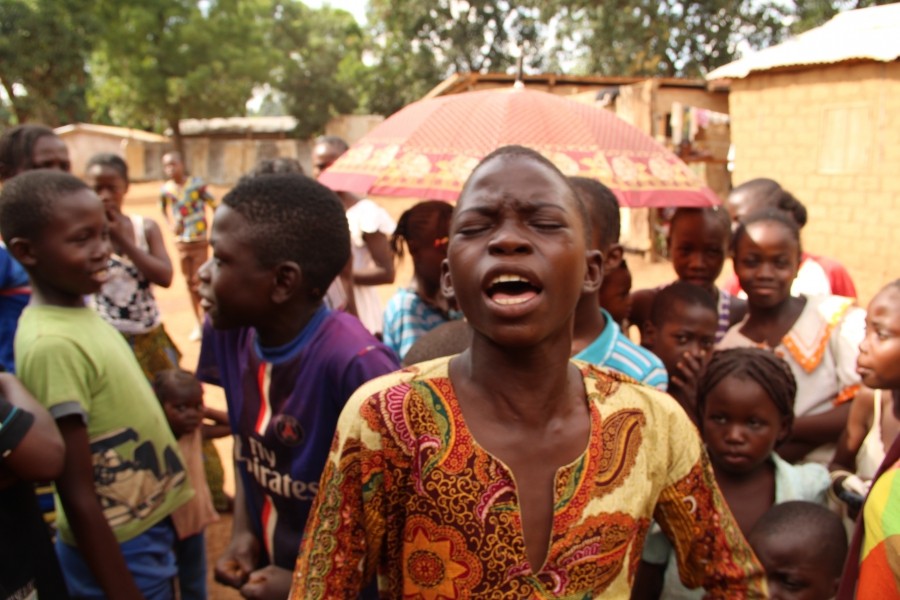 Fortuné pours his heart into singing a hymn outside of his home in the Miskine neighborhood in Bangui.
