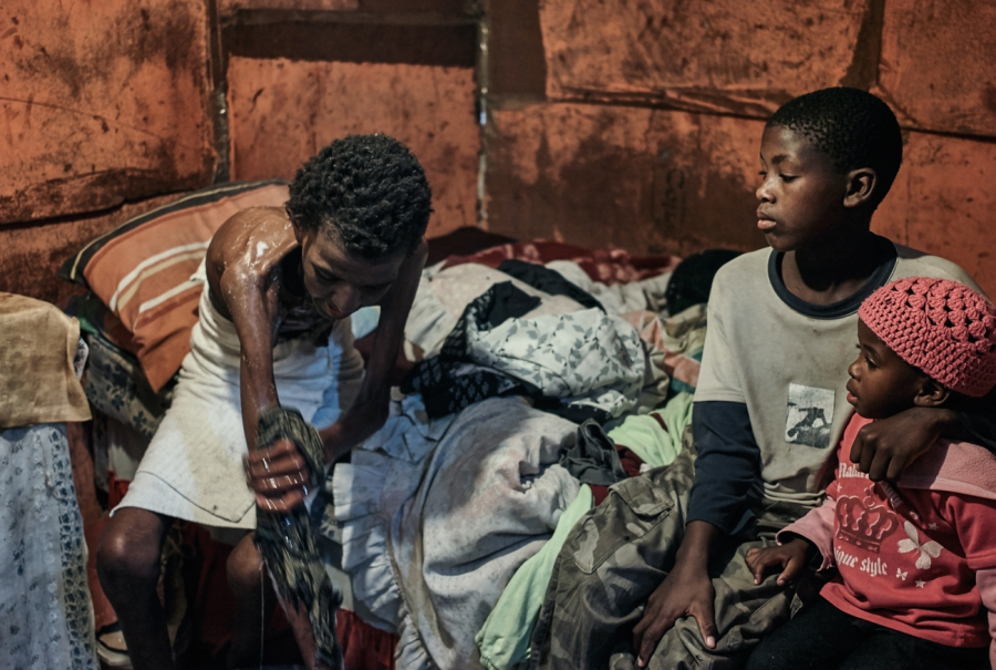 Lutango Nompumelelo, 42, washes before going to the hospital. She shared her bed with her children Mcepisi and Akhona. 2013, Gugulethu, Cape Town.