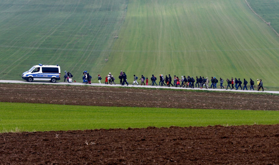 German police escort migrants to a registration center after they crossed the Austrian-German border in Wegscheid near Passau, Germany, Oct. 20, 2015.