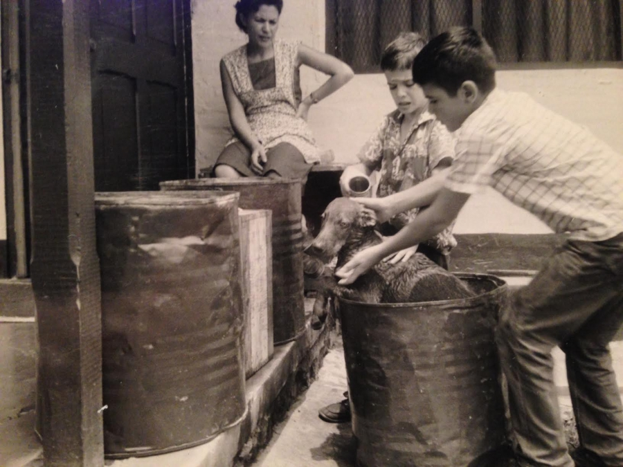 Brothers John and George Campbell wash their pet dog while their mother, Hortensia, watches. Photo taken in Segovia, Colombia.
