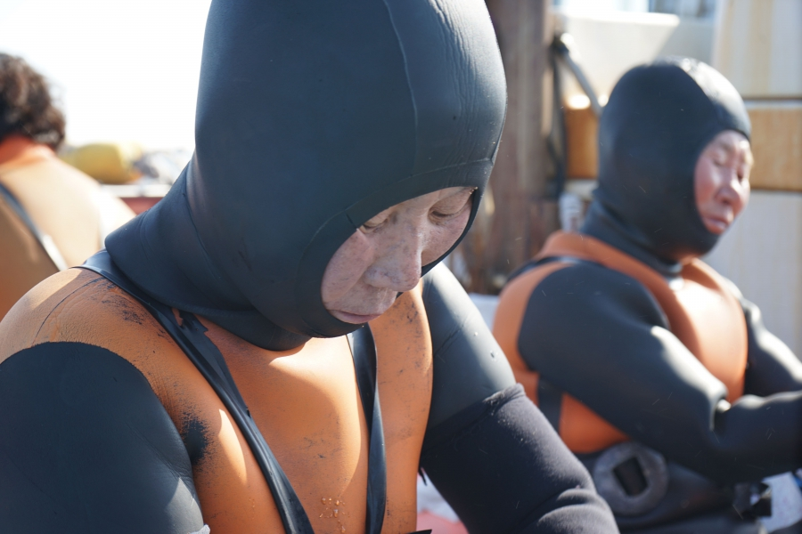 Haeynyos preparing for their dive. Commerical fisheries have largely emptied the waters so the divers have to travel further out to find their catch.