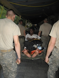 Paratroopers from the 82nd Airborne carry Nathalie LeBrun to a military ambulance.