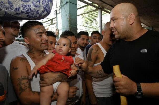 Man with tattoos holding baby, talking to another man in black T-shirt