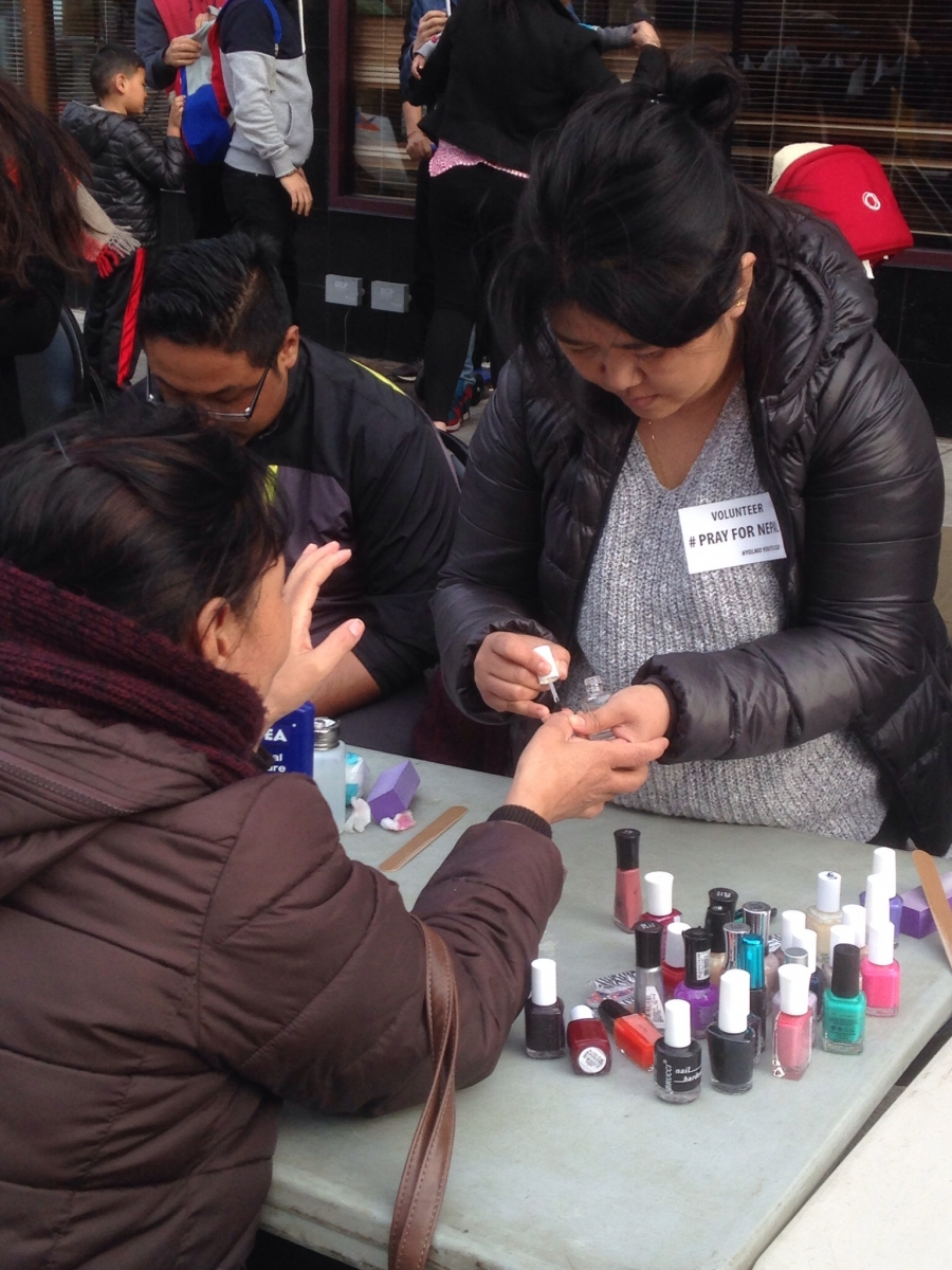Women paint nails to raise money.