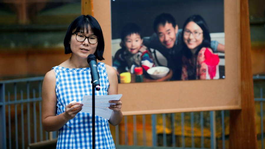A woman speaks in front of a microphone. Behind her is a large image of her, with her husband and young son.