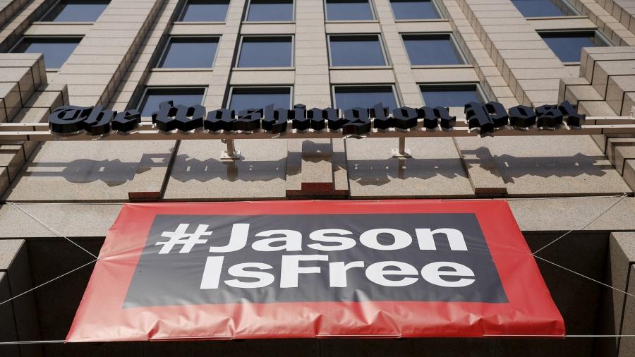 A large banner hangs below the Washington Post building reading #JasonisFree
