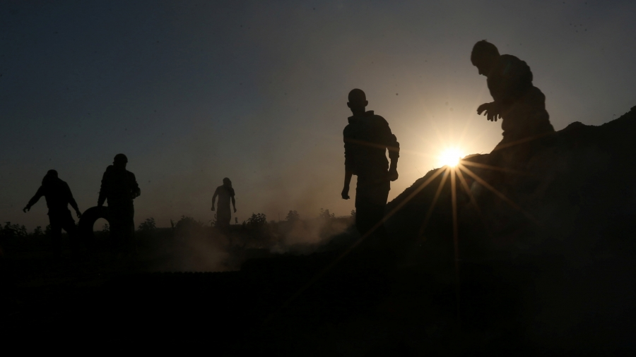 People are silhouetted against the sun as some smoke surrounds them. One man on the left rolls a tire.