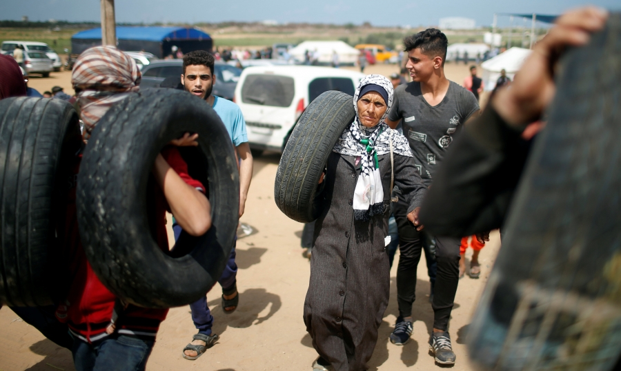 Palestinian demonstrators carry tires during a protest against US embassy move to Jerusalem.