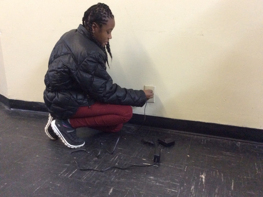 Arany plugs her mother's ankle bracelet into the wall.