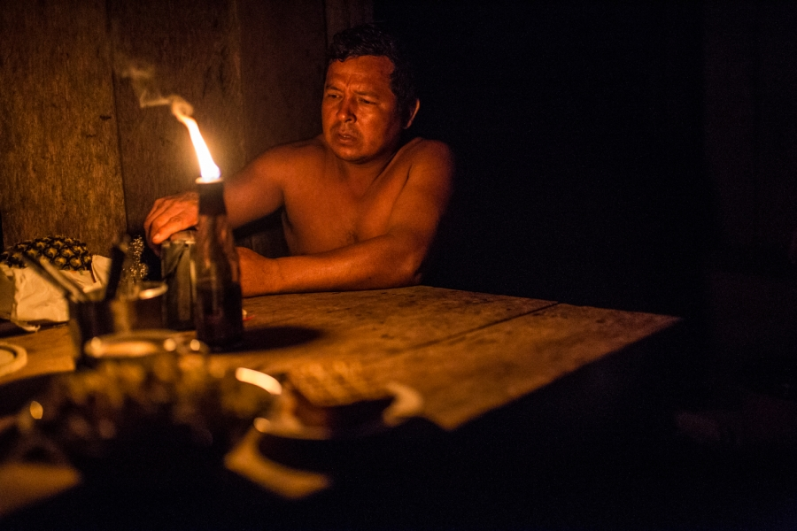 A man sits in a shack lighted by a candle.