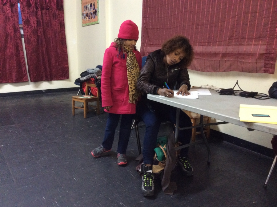 Julia fills out forms at Gregoria Flores' immigration clinic with daughter Nazary.