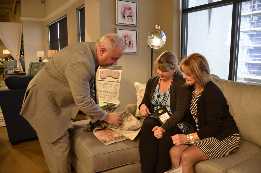 A salesperson with Klaussner Home Furnishings shows sofa fabric choices to potential customers at the company's showroom in High Point, NC.