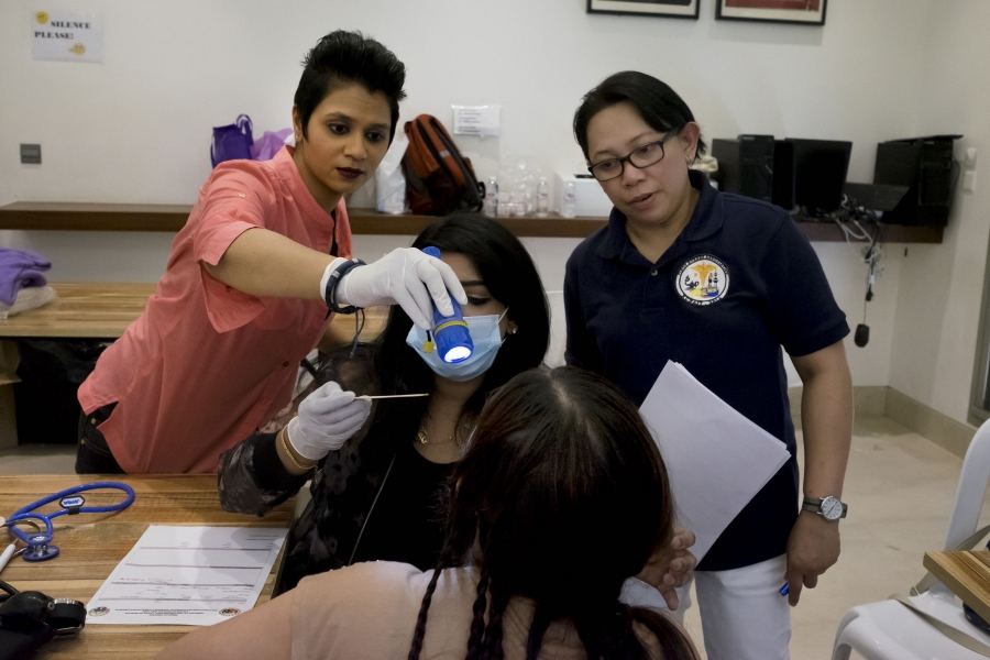 A group of doctors evaluates a patient during a medical mission at the shelter.Around 100 Kuwaitis and Filipino volunteers agreed to help treat over 1,000 domestic workers taking refuge therein March. Credit: Alisa Reznick/PRI