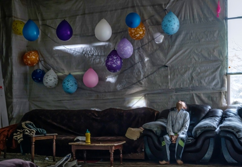 A young boy sits on a couch, looking toward the ceiling, where a string of balloons hangs