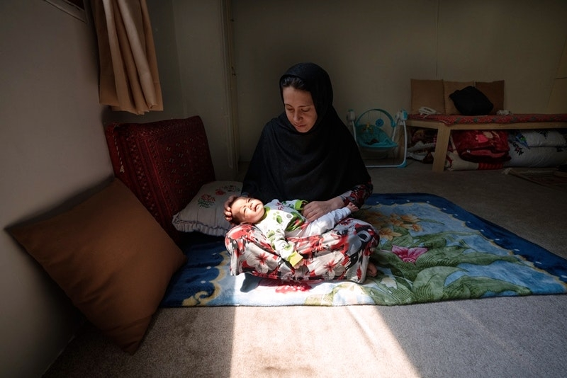 A woman sits on the ground and holds a baby in her lap. Sun shines on her in a room that is otherwise dim.