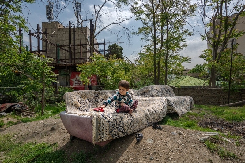 A young child sits on a couch outdoors
