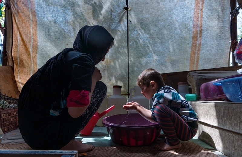 A woman and young child squat around a bowl of water