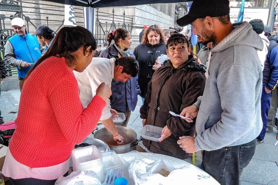 Paola Sarabia, in brown coat, offers warm stew to people lined up in front of Argentina's congressional building. Sarabia hopes lawmakers will see how many Argentines rely on food banks.