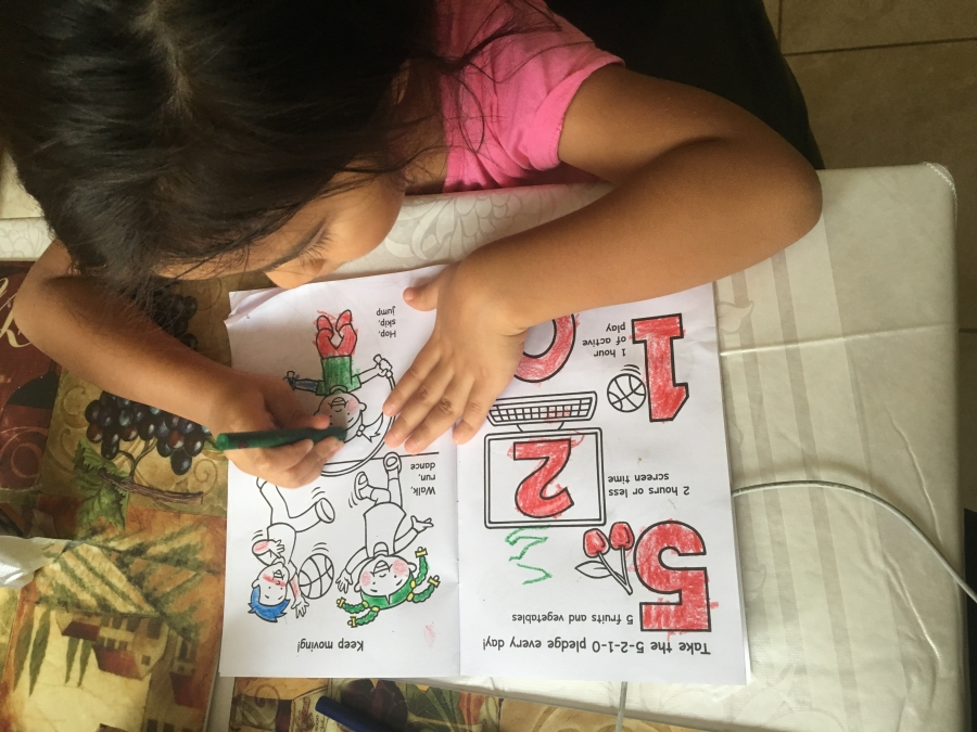 overhead view of young girl coloring in coloring book