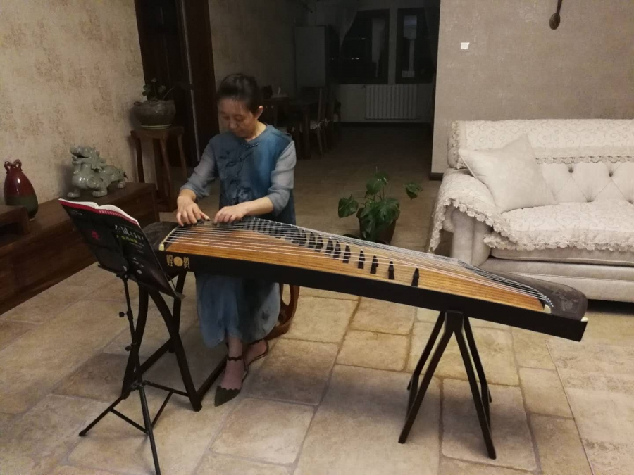 A woman in a blue dress sits facing the camera and a music stand and plays guzheng, a Chinese traditional instrument that looks like a small table with strings on it