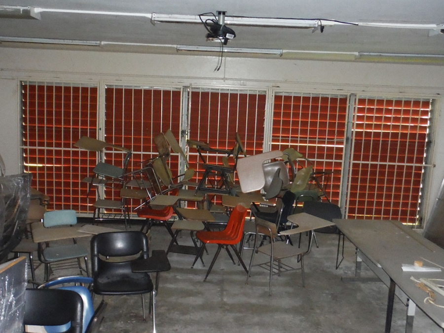 A bunch of chairs piled up in a classroom.