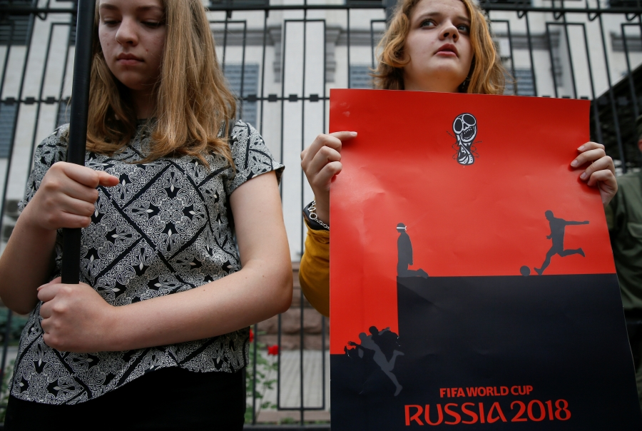 A demonstrator holds a poster during a rally demanding the liberation of Ukrainian film director Oleg Sentsov by Russia, in front of the Russian embassy in Kiev, Ukraine, June 13, 2018.