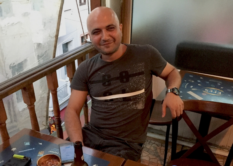 Bilal Dündarlioğlu, a 34-year-old information technology engineer in Turkey, sits at a cafe table.