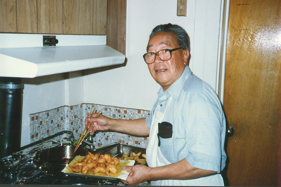 Elderly man cooking and looking at camera