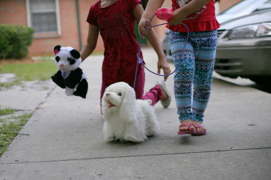 Tow young girls playing on sidewalk with toy animals, faces not shown