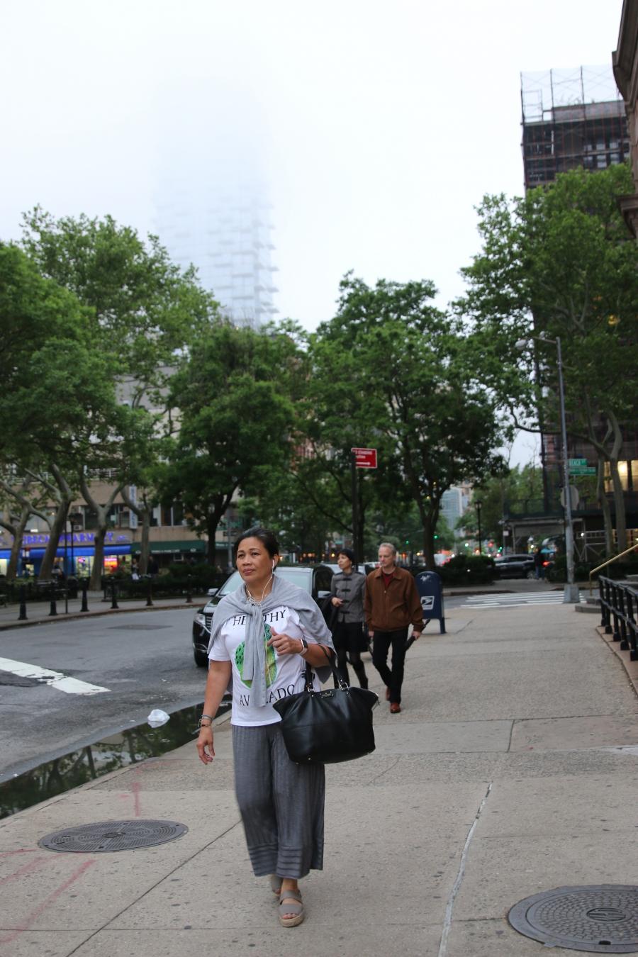Woman walking on city sidewalk holding purse