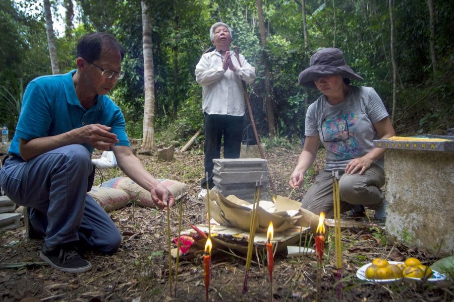 Three people stand in a jungle around a gravestone
