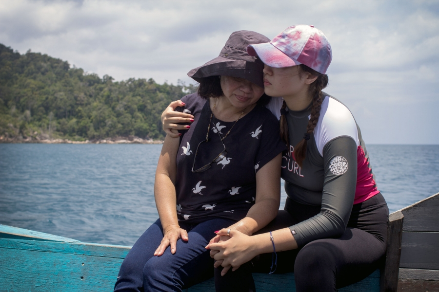 A younger woman wraps her arms around an older woman as they sit on the edge of boat.