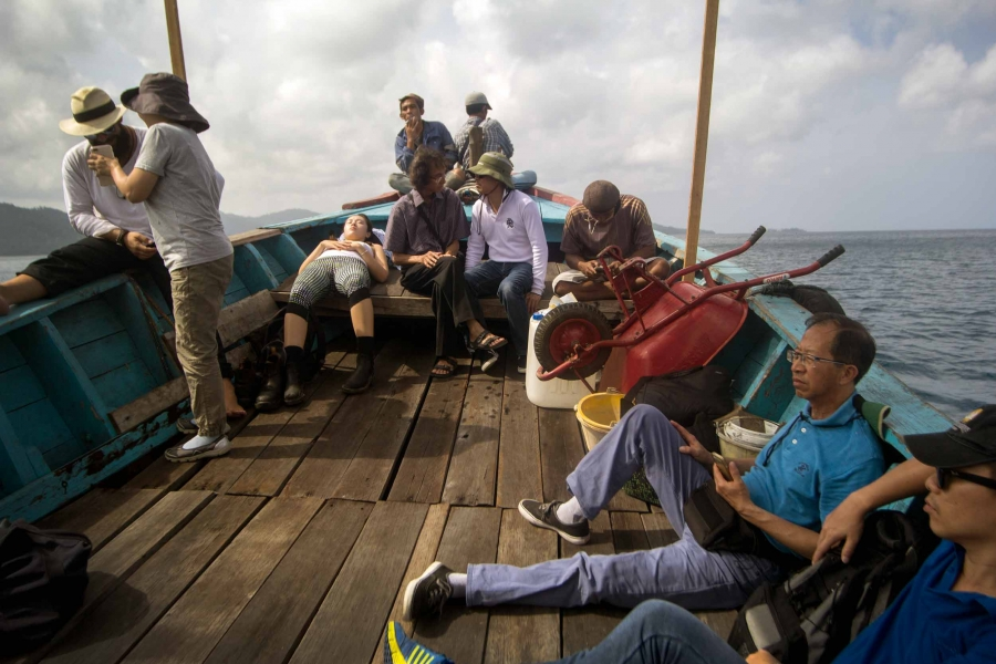 Ten people sit on the wooden deck of small boat.