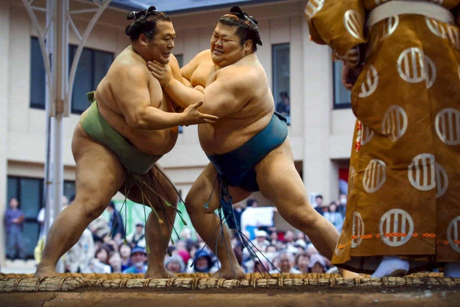 Two sumo wrestlers compete in an outdoor ring while a crowd watches.