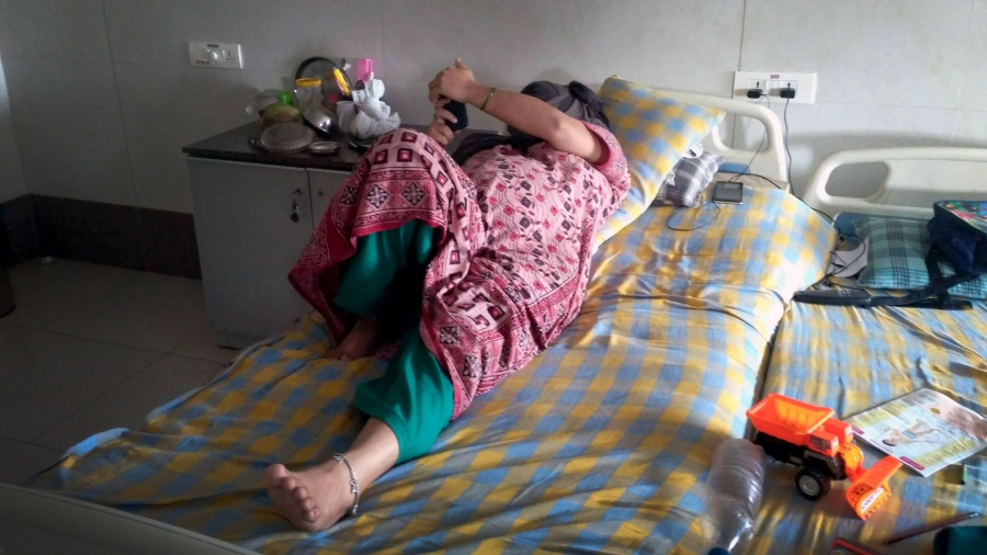 A woman lays on a hospital bed and turns her face away from the camera, reading the cell phone in her hand.