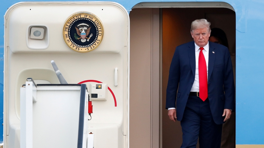 US President Donald Trump is shown exiting Air Force One with the door of the aircraft ajar.