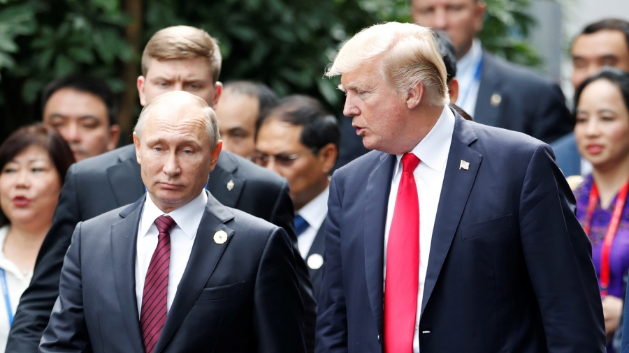 US President Donald Trump and Russian President Vladimir Putin are seen walking side-by-side surrounded by other officials.